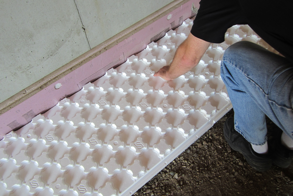 Worker installing Heat Sheet radiant flooring system